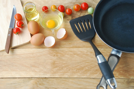 flipper: kitchenware are including frying pan, flipper used in frying, spoon, fork, knife, wooden block, eggs and fresh tomatoes with vegetable oil in glass container are placed on a wooden background in top view.