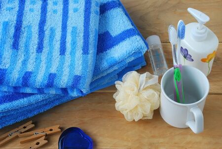 bath cream: blue stripe towels and toothbrush in a glass with shampoo, bath cream and bath scourers placed on a wooden background decorated with clothes peg and blue stone glass