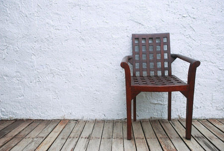 singly: One wooden chair on the old brown wooden floors and white rough walls, look lonely and isolated.