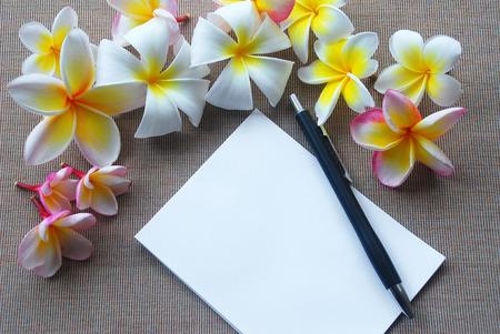 lineas verticales: Varios Plumeria flor yacía sobre tela marrón con unas pequeñas líneas verticales incluso con una pequeña nota de papel y lápiz de color azul oscuro