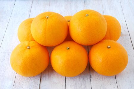 regularity: Group of oranges sort stacked on white wooden floor. Creating a sense of regularity and unity.