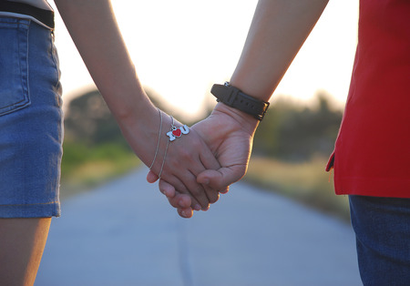 feel affection: Lovers walk and holding hands on the road in evening. They have the necklace in heart shape is mean I love You in concept about lovers Stock Photo