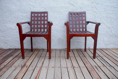 A couple old brown wooden chairs decorated on the old wooden floor with rough white wall.