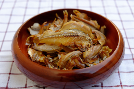 small sea fish are fried crispy and placed in a brown wooden bowl look appetizing.