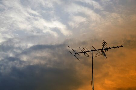 Silhouette of an old television antenna in the sky with rain clouds in the evening. Stock Photo