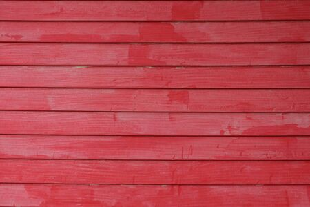Old wooden wall in the horizontal, painted red and uneven look sloppy
