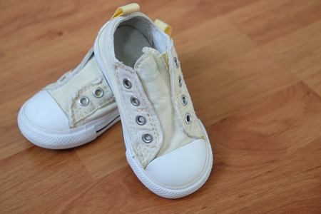 Children sneakers have a pale yellow, look old and arrange on a brown wooden floors.
