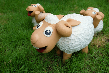 Cute sheep from clay doll, They have a happy face and smiling are decorated on a green lawn. Stock Photo
