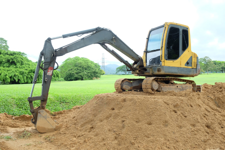 Small crawler loader is parking on the mound, there are green trees in the background.