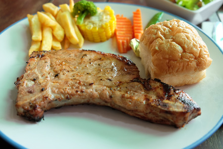 Pork chop steak in white plate. Including bread, french fries and vegetables in the blur background. This steak is in restaurant. Stock Photo