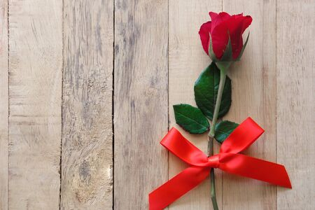 Single red rose tied with a red ribbon. placed on brown wooden background.