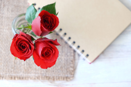 Three red rose in a vase in the top view on sackcloth and notebook in blurred background.