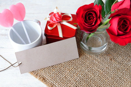 Pink lollipop, red gift box and a red rose lay on sackcloth with blank brown paper for write a message for valentine day.
