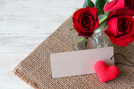Red roses and heart shaped knitted from yarn with label paper for write message decorated on sackcloth.