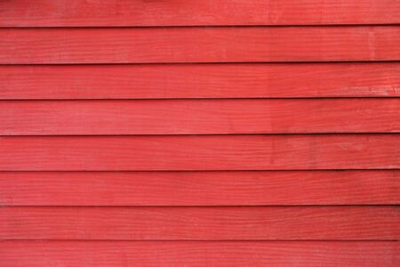 Dirty old wooden wall in the horizontal, painted red and uneven look sloppy