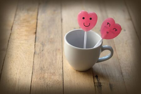 Pink heart shaped lollipops in lover concept have a happy face and decorated in a small white cup of coffee. Placed on a wooden floor, Adjust photo in retro style