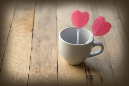 Pink lollipops in heart shaped decorated in a small white cup of coffee. Placed on a wooden floor, Adjust photo in retro style Stock Photo