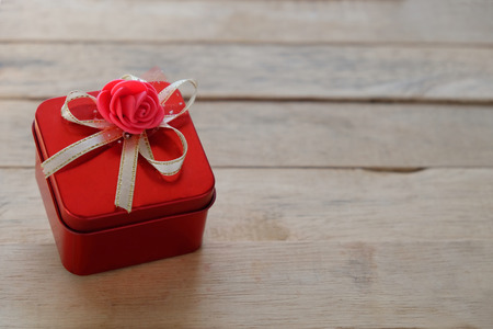 Lovely red gift box from top view, place on a brown wooden floors. The concept of Valentine's Day.