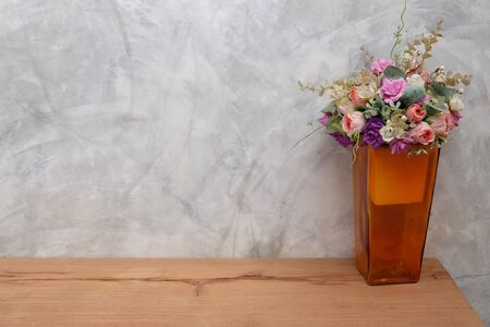 Vase tall shape in orange have a sweet colorful flowers in vintage style. Decoration on a wooden floor with gray cement wall as a backdrop.
