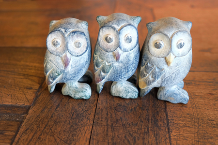 Three small owl statue. Decoration on brown wood floor. Look like a friendship or teamwork concept. Stock Photo