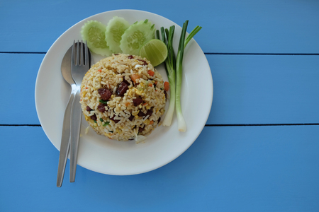 Fried rice with Chinese sausage in a white dish. Decorated with onion, cucumber and lemon slice with spoon and fork lay on blue wooden table in top view. Stock Photo