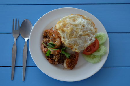 Fried shrimp with garlic, fried egg and cooked rice in a white dish. Decorated with tomato and cucumber slice with spoon and fork lay on blue wooden table in top view.