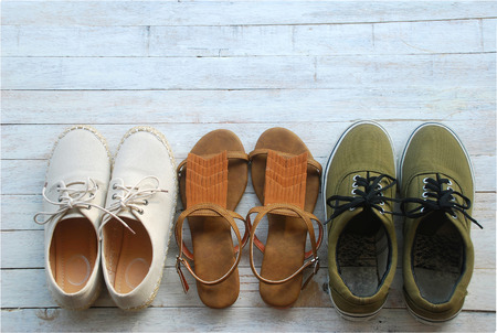 Three pairs of women's shoes are casual shoes in light brown, dark brown leather shoes in vintage style and dark green sneakers lay on the wooden floor in the top view. Stock Photo