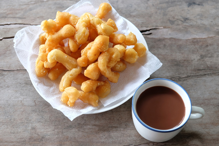 deep-fried dough stick with a cup of hot chocolate. This is a simple Asian breakfast. placed on wooden table in top view.
