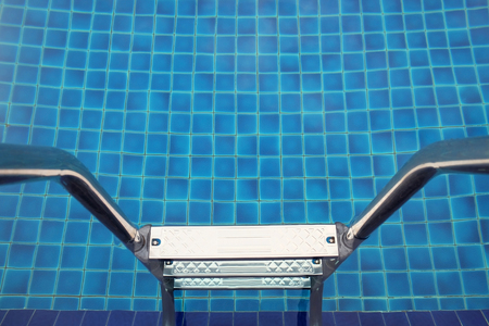 swimming pool with blue tiles and handrail and stainless stairs it look is balanced.