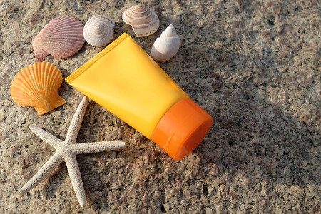 Sunscreen is placed on the beach in the morning sunlight. Decorated with shell and starfish.