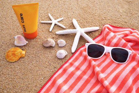 The towel has a long orange stripes and white sunglasses with sunscreen decorated with shell and starfish on the sand.
