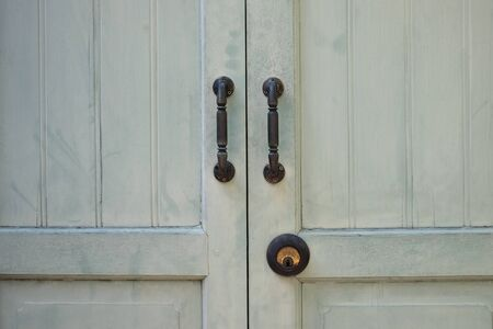 The old wooden door have with two door handles steel, shut and lock  with the old key and rust.