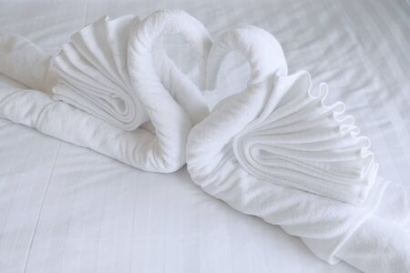 White towels are arranged as two swans and a heart shaped. Decorated on the bed to welcome guests staying in the hotel. Stock Photo