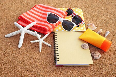 Summer on the beach concept. Arranged the towels, sunglasses, sunscreen and notebooks on the sandy beach, decorated with starfish and shells in the summer sun.