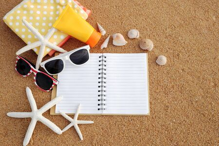 Summer on the beach concept. Arranged the towels, sunglasses, sunscreen and blank page of notebooks on the sandy beach, decorated with starfish and shells in the summer sun.