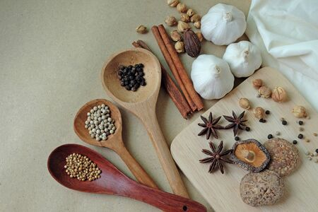 Many spices and dried herbs, such as pepper, shiitake mushroom, cinnamon, coriander seeds, cardamom and garlic are aromatic ingredients. Decorated on wooden spoons and wooden plates on top view.