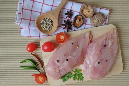 Two pieces of raw chicken breast, placed on a wooden cutting board. Decorate with pepper in wooden spoon, star anise and dried shiitake mushroom, tomato, chilli and ​coriander leaves in top view.