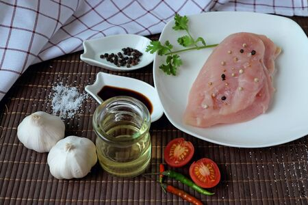 Raw chicken breast, placed on white plate with coriander leaves. Decorate with soy sauce, salt, black pepper, soybean oil, fresh chilies, garlic and sliced tomatoes.