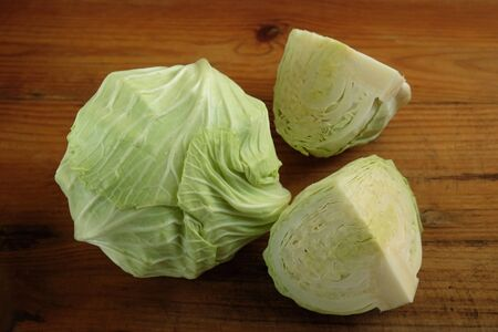 Fresh green cabbage and cut cabbage placed on a brown wooden background