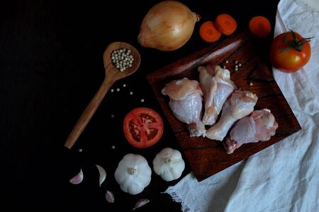 Raw chicken wings and ingredients for cooking such as onions, tomatoes, sliced carrots Including garlic and pepper. Placed on a black wooden background