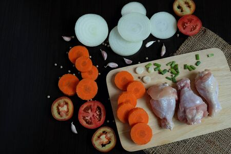 Raw chicken wings on wood cutting board and ingredients for make chicken soup such as sliced onions, tomatoes and carrots Including garlic and pepper. Placed on a black wooden background in top view