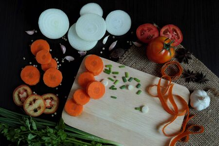 Various vegetables are chopped, such as carrots, onions, tomatoes, and pepper, garlic, and anise, arranged around a wooden cutting board. Then decorate with spring onion, coriander and carrot peel. Stock Photo