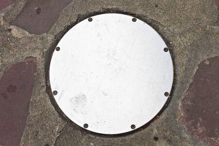 drain: Circle Metal drain cap on sidewalk Stock Photo