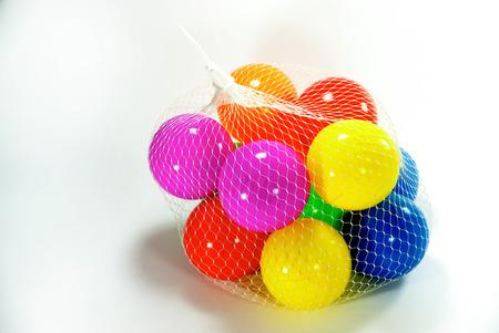 sac: vivid plastic balls in white net sac on white scene,shallow focus