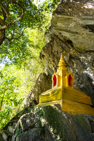 golden pagoda infront of natural cave in the forest,Chiangrai,Thailand photo