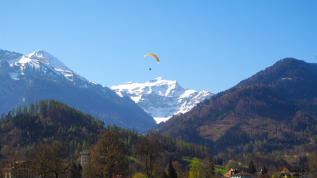 Paraglider with snow mountain and blue sky background Imagens