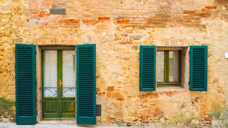Green window and door with antique building in Monteriggioni Stock Photo
