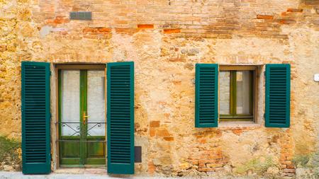 Groen venster en deur met antiek gebouw in Monteriggioni