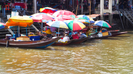 Food boat with colorful umbrella at Ampawa Imagens
