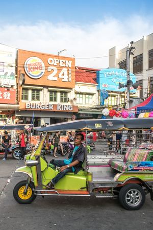 BABGKOK, THAILAND - APRIL 30, 2018 : nidentified driver of  tricycle taxi (Tuk Tuk) at Khao San wating for tourists in front of Burger King resterant Editorial